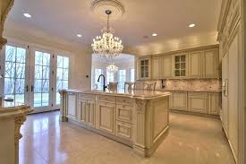 cream and brown kitchen cabinets traditional kitchen with cream cabinets chandelier marble counter and large island