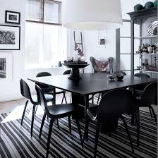 dining room with black and white striped rugs dining table chairs cupboard and