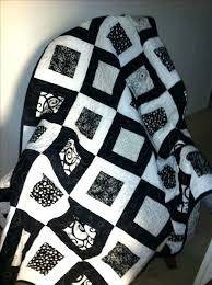black and white quilt made from 5 squares and bordered with 2 1 green and white