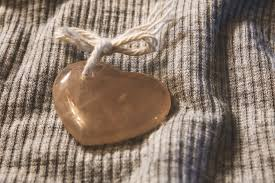 brown heart shape stone on top of gray textile preview