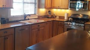 having a hard time with picking a granite or quartz countertop to go have natural hickory cabinets and brown tile floor what do you suggest