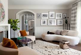 Living room with dark wood floors and large diagonally situated black and  white rug. Fireplace
