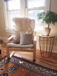 off white poang chair with pillows and a fur cover for a living room