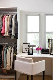 walk in closet designed with a white waterfall vanity and a white chair under a window beside a built in shelving system with stacked clothing rails