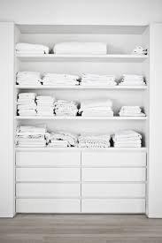 a built in closet with open shelving and ikea malm dressers for smaller items is