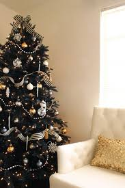 refined black Christmas tree with striped ribbon, silver and gold ornaments