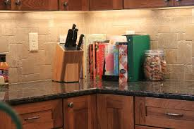 a tumble marble backsplash under cabinet lighting granite counters and wood stained cabinets update cabinet lighting backsplash