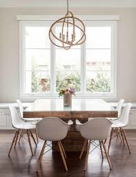 contemporary dining room features a rope sphere chandelier hanging over a square wood dining table with gl top lined with eames molded plastic armchairs