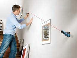 man working with laser level that is attached to the wall for picture hanging