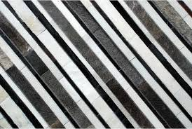 top detail of white gray and black leather area rug in stripes