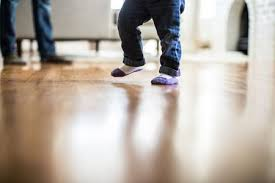 a small child sliding on their socks on hardwood