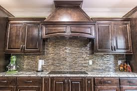 delicatus white granite countertop with glass tile backsplash and dark brown cabinets