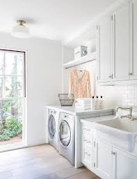 white laundry room features white cabinets adorned with vintage latch hardware paired with carrera marble countertops