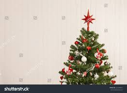 Detail of a beautiful christmas tree set against a wooden wall for copy  space