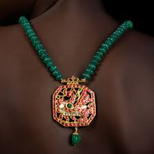 traditional south indian peacock pendant of 22k gold studded with rubies emeralds and uncut diamonds a single emerald droplet dangles below