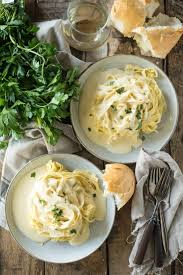 two plates of fettuccine alfredo on gray plates on wood table with forks bread and