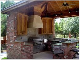 Classic mahogany unstained kitchen cabinetry with stacked stone patio canopy as well as black polished outdoor grill island with custom wall mount range