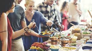 people with blue plates reaching with large utensils to grab food off a buffet table of