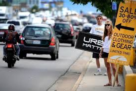 sign twirler cities businesses go round and round on twirling signs of