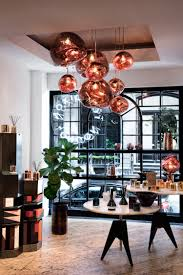 the ground floor of tom dixon s new york showroom with mirrored copper pendants and lighting objects