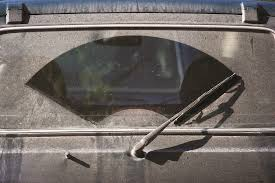 a rear windshield wiper with dust all over the rear window except where the wiper sweeps
