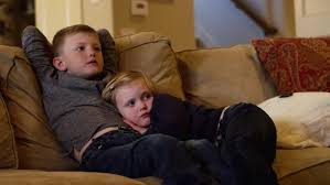 family watching tv at night. young siblings sitting close together on the couch and watching television - 4k stock video clip family tv at night