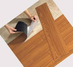 installing faux wood vinyl flooring that looks like wood planks with brown color for kitchen or living room spaces ideas