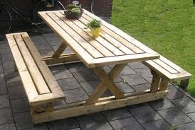 a wooden picnic table with plants on the top