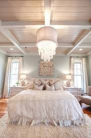 eclectic white bedroom with barn beams and crystal chandelier