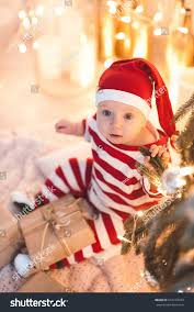 Cute baby girl 1 year old sitting under Christmas tree with lights and present wearing striped Baby Girl Year Old Stock Photo (Edit Now) 516270319