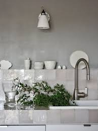 wall sconce white cone shade grey wall paint square mother of pearl tile kitchen backsplash and countertop stainless steel faucet cups drinking glasses