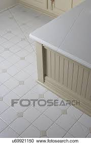 bathroom detail of tile floor edge of wainscot surround on bathtub in cottage style bath