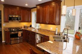 brilliant brown finished kitchen cabinets also marble countertops as well as yellow wall kitchen paint colors added wooden flooring installations ideas