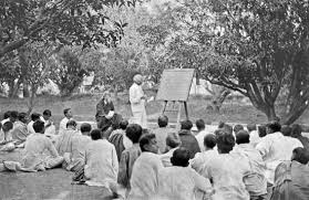 rabindranath tagore biography facts com rabindranath tagore seated to left of man at blackboard at an open