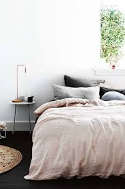 Bedroom: grey and pale pink bed linen, dark floorboards, white walls,  copper lamp with exposed lightbulb