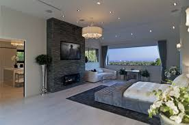 Modern Gray Bedroom With Dark Stone Wall And Modern Small Black Fireplace  Also Large Glass Window. «