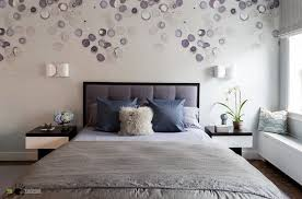many round off white and purple decorations on a wall behind a double bed