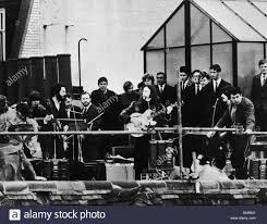 beatles on the rooftop of their apple headquarters in london saville row giving their last ever apple head office london