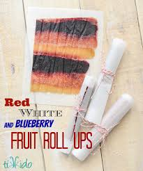 rolls of homemade fruit roll up on parchment paper secured with red and white baker s twine