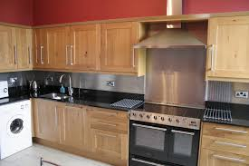 stainless steel backsplash idea black countertop electric stove unfinished  wood cabinetry white ceramic tiles for floors