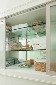 built in bathroom cabinet with glass shelves