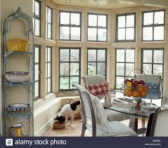 Narrow Metal Shelving Beside Large Bay Window In Country Dining - Bay window in dining room