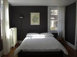 This grey bedroom has dark grey walls.