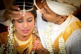 the groom applies a red mark on the bride s forehead