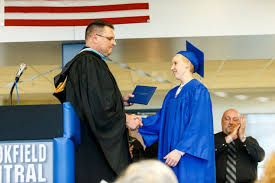 special graduation ceremony held for student battling cancer  andrew wernicke and principal brett gruetzmacher shake hands as andrew receives his diploma
