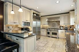 kitchen white engraved kitchen cabinets on light neutral tone tile floor with dark counter tops