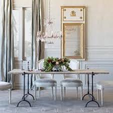 romantic dining room with rustic dining table with delicate iron legs crystal chandelier antique replica dining chairs and french trumeau mirror