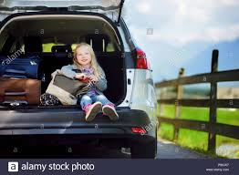 adorable little sitting in a car before going on vacations with her pas kid ready to travel by car