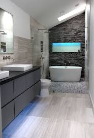 Amazing master bath retreat with dark stacked stone back wall feature and  glass area for shower with dual shower heads and deep soaking tub. Modern  master ...