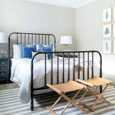 black spindle bed with gray striped jute rug